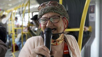 Marlene Alfonso, una abuela venezolana de 69 años que se hace llamar Cindy sin dientes, canta sobre la vida de los migrantes de su país con la esperanza de recibir propinas de los viajeros en el Transmilenio, el sistema de autobuses públicos atestado y asotado por el crimen en Bogotá, el martes 3 de noviembre de 2020.