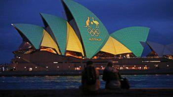 Una pareja observa la Ópera de Sídney iluminada con los colores del equipo australiano durante la campaña de Brisbane para ser sede de los Juegos Olímpicos del 2032