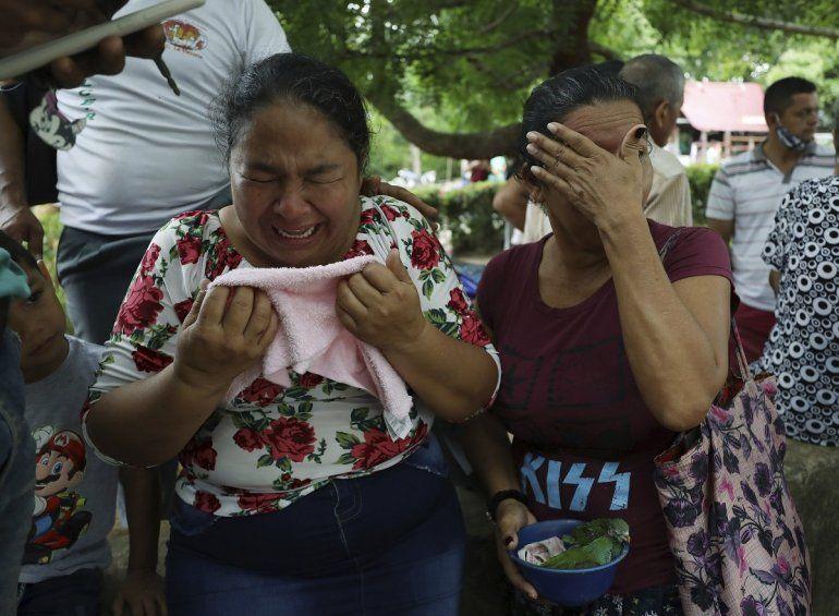 Mujeres lloran mientras explican que tres de sus familiares fueron asesinados el día anterior en El Ripial