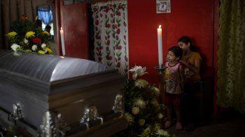 Dos de las seis hijas del periodista asesinado Julio Valdivia de pie junto a su ataúd durante un velorio en su casa ubicada en Tezonapa, Veracruz, en México, el jueves 10 de septiembre de 2020.