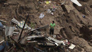 Un hombre intenta rescatar algo de lo que undía fue su hogar, destruido por lasinundaciones y los deslaves asociados al paso de la tormenta tropical Amanda por El Salvador.