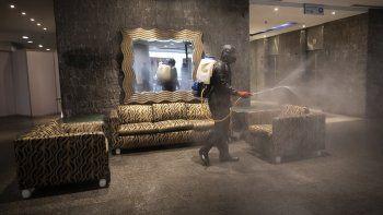 Un trabajador municipal desinfecta el vestíbulo del hotel Alba el miércoles 7 de abril de 2021, el cual será utilizado para atender a pacientes con COVID-19, en Caracas, Venezuela.