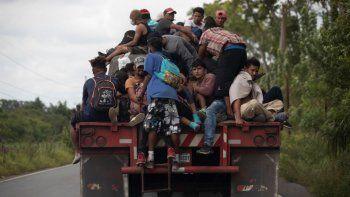 En esta fotografía de archivo del 2 de octubre de 2020, los migrantes viajan en la parte trasera de un camión de carga que redujo la velocidad para darles la oportunidad de subirse a Río Dulce, Guatemala. Mauro Verzzeletti, director de la Casa del Migrante en Ciudad de Guatemala, dijo que las tormentas Eta e Iota aumentarán la pobreza además de la violencia que la gente ya enfrenta, obligando a más a migrar.