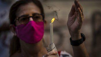 Una mujer con mascarilla sostiene una vela encendida durante una misa católica transmitida por radio en honor a la Virgen de la Caridad del Cobre, en su fiesta en La Habana, Cuba, el martes 8 de septiembre de 2020.