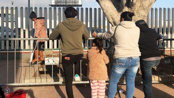 En esta fotografía del miércoles 8 de enero de 2020, unas personas que buscan solicitar asilo en Estados Unidos esperan en un puente fronterizo de Tijuana, México.