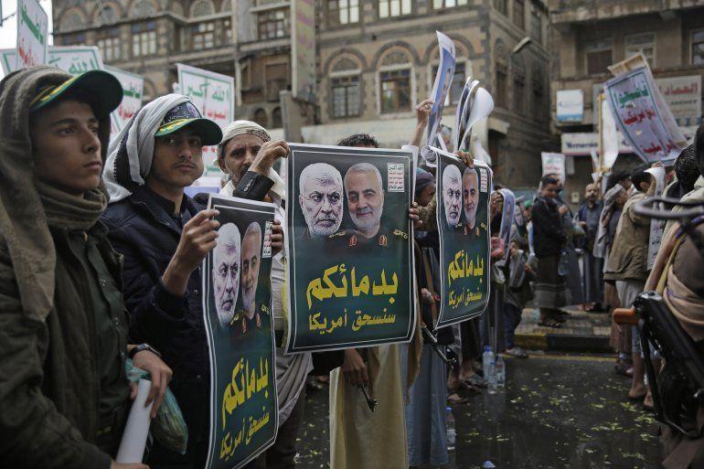 Hutíes chiíes de Yemen sostienen carteles con las imágenes del comandante paramilitar iraquí Abu Mahdi al-Muhandis