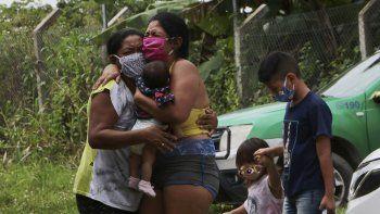 Familiares lloran a un lado de la carretera mientras esperan a que una funeraria recoja el cuerpo de Arlen Laranjeira Bezerra, de 39 años y víctima del coronavirus, que falleció tras huir de la sala de urgencias del hospital Delphina Rinaldi Abdel Aziz en Manaos, en el estado brasileño de Amazonas, el 5 de mayo de 2020.