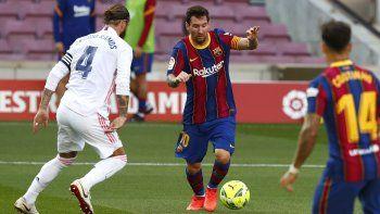 El delantero argentino Lionel Messi disputa el balón con Sergio Ramos del Real Madrid en el partido por La Liga de España, el sábado 24 de octubre de 2020.
