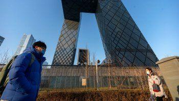 Fotografía de archivo del 4 de febrero de 2021 de personas caminando frente a las oficinas generales de la televisora estatal china CCTV y de su brazo para el extranjero CGTN, en Beijing.