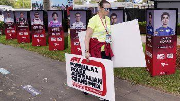 Una mujer retira carteles tras la cancelación del Gran Premio de Australia de Fórmula1 en Melbourne el viernes, 1 de marzo del 2020, debido al brote de coronavirus.