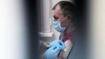 Un trabajador de la salud administra a un hombre una dosis de la vacuna rusa Sputnik V (Gam-COVID-Vac) contra el COVID-19 en un centro de vacunación en San Petersburgo, el 21 de febrero de 2021, mientras Rusia lanzaba un COVID-19 masivo. Campaña de vacunación para personas sin hogar.
