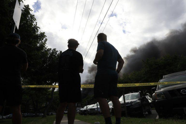 Transeúntes observan el humo que sale de una casa incendiada después de un tiroteo y una disputa doméstica en una residencia de Hibiscus Road