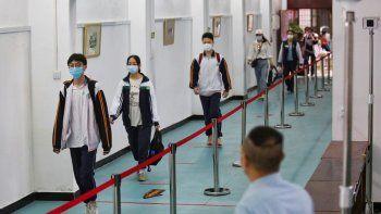 Estudiantes con mascarillas y a cierta distancia unos de otros para evitar la propagación del coronavirus llegan a una secundaria el miércoles 6 de mayo de 2020 en la ciudad de Wuhan, provincia de Hubei, en el centro de China.