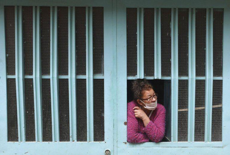 Una mujer se asoma por la ventana de su casa mientras espera la llegada de comida gratis del gobierno municipal durante una cuarentena para ayudar a contener la propagación del coronavirus en Bogotá