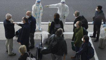 Un trabajador, equipado con un traje de protección, dirige a los miembros de un equipo de expertos de la Organización Mundial de la Salud a su llegada al aeropuerto de Wuhan, en la provincia de Hubei, en China, el 14 de enero de 2021.