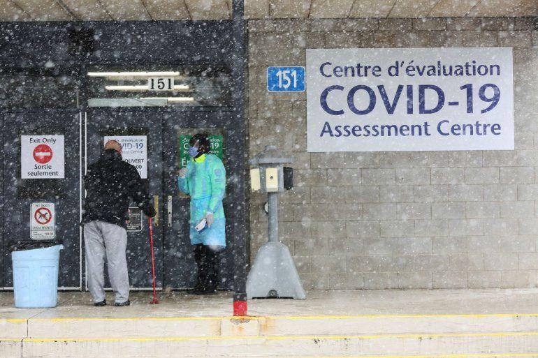 Un oficial de Salud Pública de Ottawa (derecha) habla con la siguiente persona en la fila en el centro de pruebas COVID-19