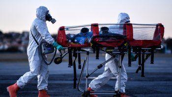 Miembros de la Brigada Militar de Bomberos de Minas Gerais (CBMMG) que usan equipo de protección, demuestran el uso de una camilla de aislamiento o camilla de burbujas, para transportar pacientes infectados con coronavirus (COVID-19), en el aeropuerto de Pampulha, en Belo Horizonte, estado de Minas Gerais, Brasil, el 22 de julio de 2020. El equipo, que puede utilizarse para transportar pacientes en aviones y ambulancias, filtra el aire que exhala el paciente además de aislarlo.