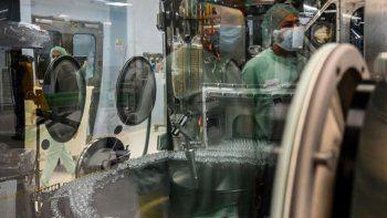 Un técnico de laboratorio, cuyo reflejo puede verse (Arriba a la derecha) supervisa las pruebas de llenado y envasado para la producción y suministro a gran escala de la vacuna candidata COVID-19 de la Universidad de Oxford, AZD1222, el 11 de septiembre de 2020 en una planta de fabricación de productos biológicos de la corporación multinacional Catalent en Anagni, al sureste de Roma, Italia.