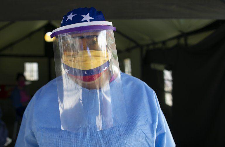 Con una mascarilla decorada con los colores de la bandera venezolana y una careta