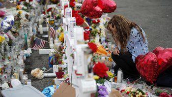 Gloria Garcés se arrodilla frente a un altar improvisado en el lugar donde ocurrió una masacre en un complejo comercial en El Paso, Texas, el martes 6 de agosto de 2019.
