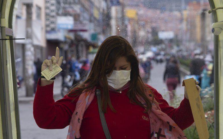 Una mujer camina a través de un túnel que rocía desinfectante durante la cuarentena que restringe a los residentes a realizar compras esenciales por las mañanas en un intento por contener la propagación del nuevo coronavirus en La Paz