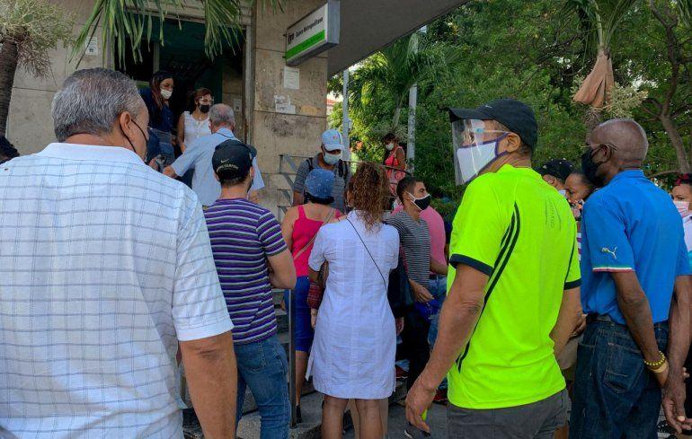 La gente hace fila frente a una sucursal bancaria en La Habana para depositar dólares estadounidenses antes de que entre en vigencia un nuevo decreto que suspenderá dichos depósitos en los bancos de Cuba.
