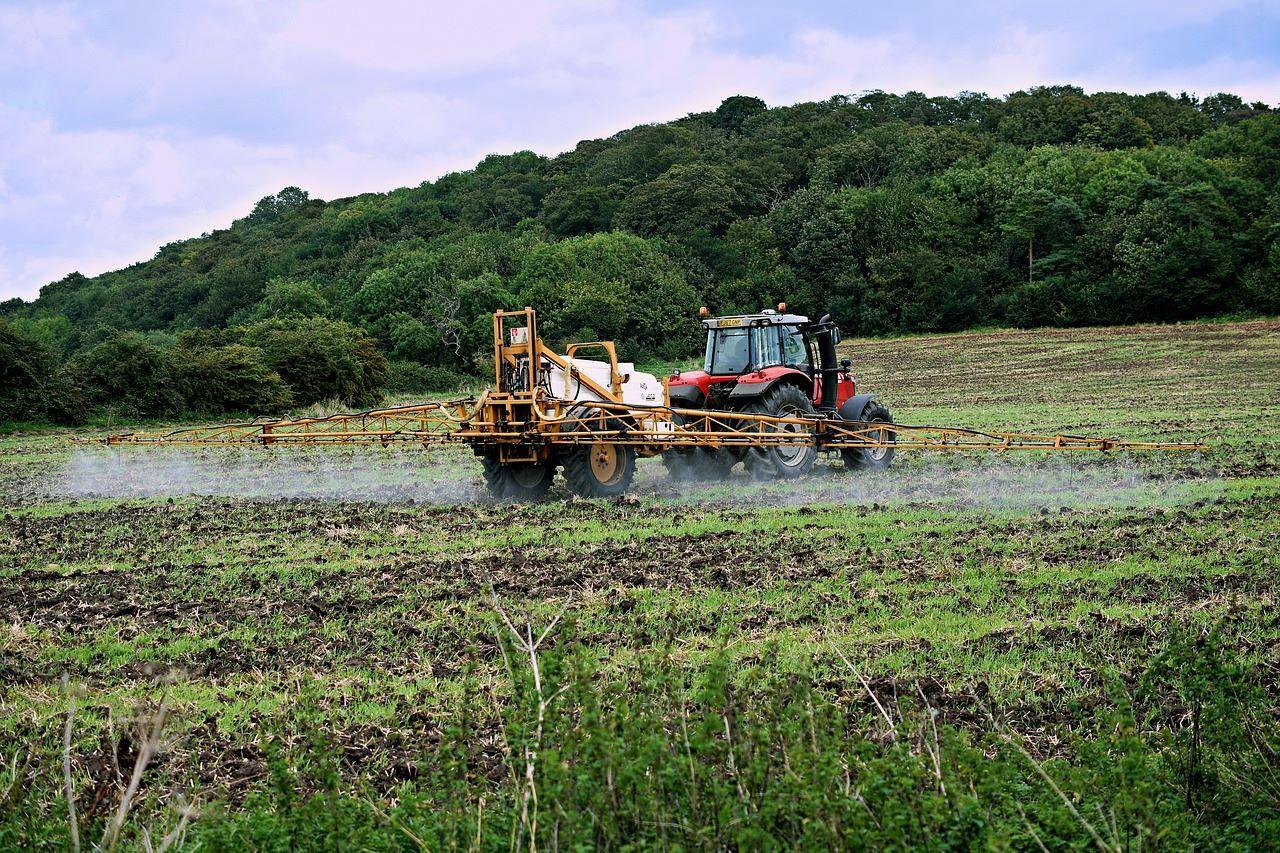 Tractor realiza riego de fertilizantes en campos de siembra.