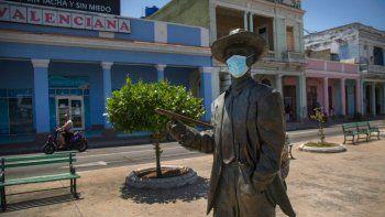 La estatua del legendario cantante cubano Benny More, con una máscara contra la propagación del nuevo coronavirus, se encuentra en Cienfuegos, Cuba, el domingo 30 de mayo de 2021.