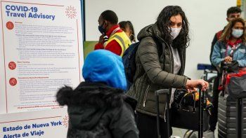 Varias personas portan mascarillas para evitar la propagación del COVID-19 mientras se preparan para abandonar la zona de entrega de equipaje en el Aeropuerto LaGuardia, el miércoles 25 de noviembre de 2020, en Nueva York.