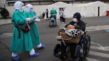 Varias personas que dieron positivo al COVID-19 son trasladadas a tiendas en el exterior del hospital del Seguro Social para seguir su tratamiento, en Quito, Ecuador.