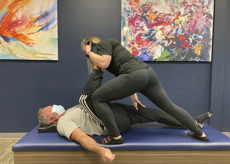 Tara Albarron estira una pierna de Ron Bryant en un estudio de Beaver Creek