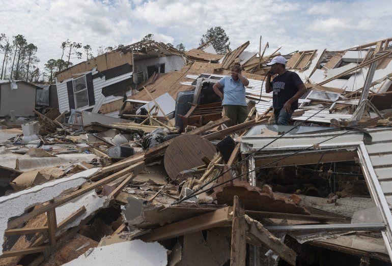 Una pareja reacciona mientras atraviesan su casa móvil destruida tras el paso del huracán Laura en Lake Charles