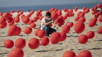 Un hombre ayuda a colocar globos rojos en la arena de la playa Copacabana durante un tributo organizado por Río de Paz para las víctimas de COVID-19 cuando el país se acerca a las 100.000 muertes por el nuevo coronavirus, en Río de Janeiro, Brasil, el sábado 8 de agosto de 2020.