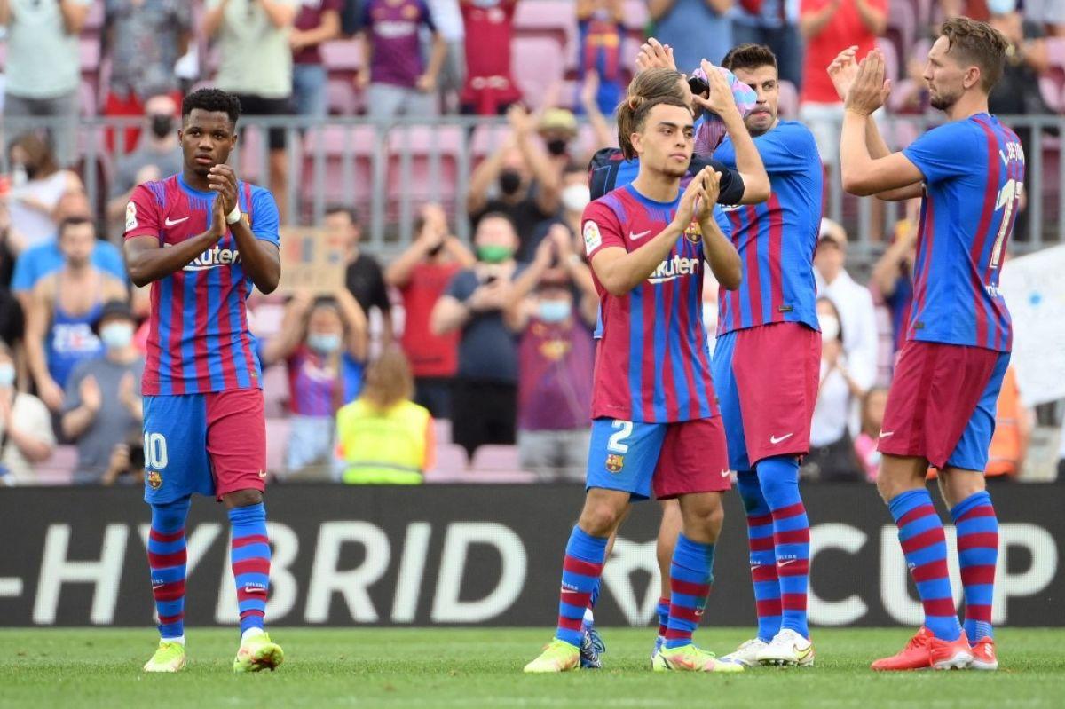 El centrocampista español del Barcelona Ansu Fati (izq.) Y sus compañeros celebran su victoria al final del partido de fútbol de la Liga española entre el FC Barcelona y el Levante UD en el estadio Camp Nou de Barcelona el 26 de septiembre.