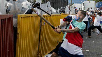 Un manifestante envuelto en una bandera costarricense y con un tubo de metal se enfrenta a la policía antidisturbios durante una protesta contra la moción del gobierno de aumentar los impuestos para llegar a un acuerdo crediticio con el Fondo Monetario Internacional (FMI), frente a la casa presidencial en San José. el 12 de octubre de 2020.