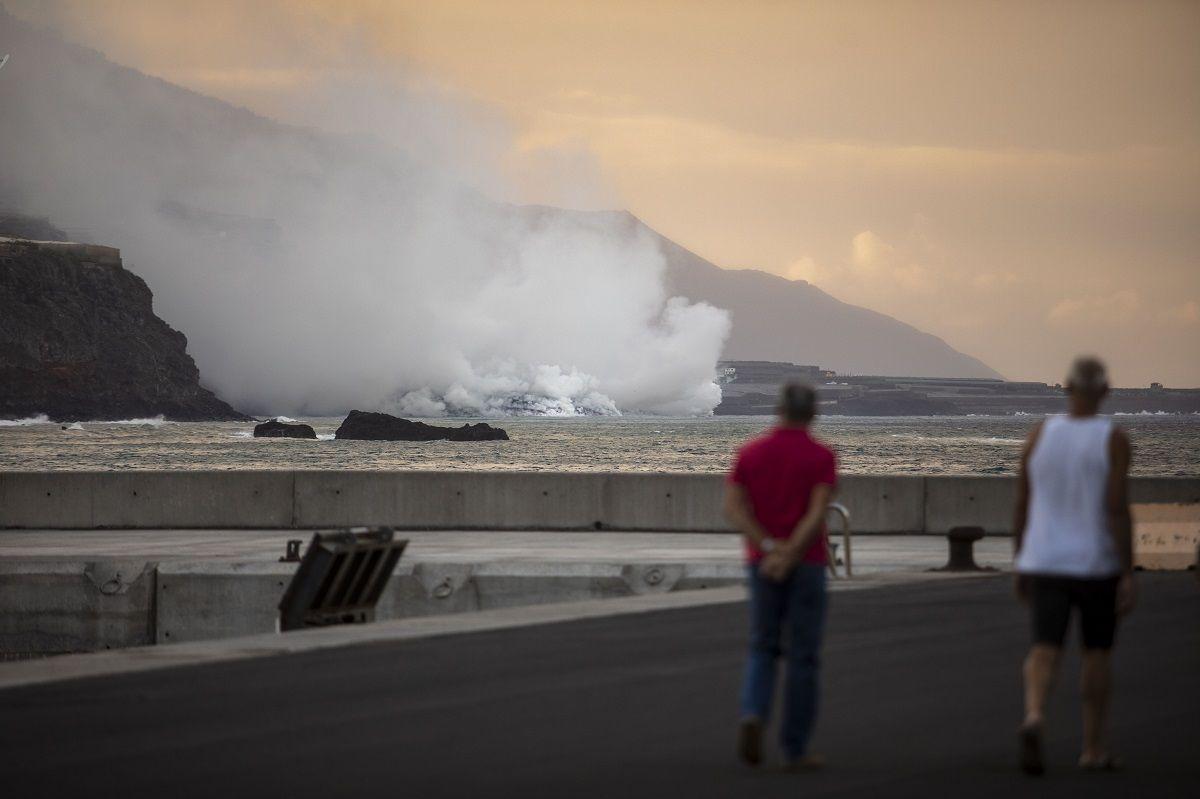 Dos personas observan la columna de humo y la lava del volcán de Cumbre Vieja a su llegada al Océano Atlántico, a 29 de septiembre de 2021, en La Palma, Santa Cruz de Tenerife, Islas Canarias, (España). La lava del volcán, que entró el 19 de septiembre en erupción, ha provocado un delta de lava que poco a poco va ganando terreno al mar a su llegada al Océano Atlántico. Las autoridades recomiendan permanecer al menos a 3,5 km de la zona ya que la entrada en contacto de la lava con el mar forma nubes blancas de vapor de agua y gases nocivos para la salud.