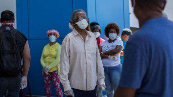 Las personas usan mascarillas pero no guardan la distancia social recomendada como medida preventiva contra la propagación del nuevo coronavirus, COVID-19. Los ciudadanos hacen cola en una calle de Santo Domingo, en República Dominicana, el 3 de abril de 2020.
