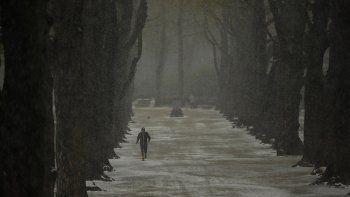 Un hombre corre bajo la nieve en el parque Cinquantenaire en un frío día de primavera en Bruselas, el martes 6 de abril de 2021. Los belgas se despertaron el martes ante una pequeña nevada en la capital, un tiempo poco habitual para esta época del año.