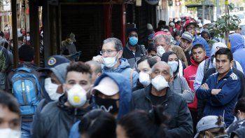 Cientos de personas usando máscaras para protegerse del coronavirus COVID-19 hacen fila en Santiago de Chile, mientras esperan un seguro de empleo para los afectados por la pandemia.