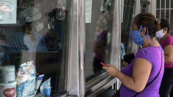 Dos mujeres que usan mascarillas como medida preventiva contra la propagación del nuevo coronavirus, COVID-19, compran suministros en una farmacia en Los Teques, estado de Miranda, Venezuela, el 16 de abril de 2020.