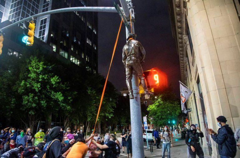 Varios manifestantes cuelgan una estatua tomada del monumento a la Confederación en el Capitolio del estado de un poste en la esquina de las calles Salisbury y Hargett en Raleigh