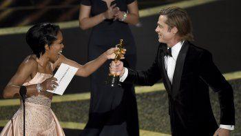 Regina King, izquierda, entrega a Brad Pitt el premio a mejor actor de reparto por Once Upon a Time in Hollywood en los Oscar el domingo nueve de febrero de 2020 en el Teatro Dolby, en Los Angeles.
