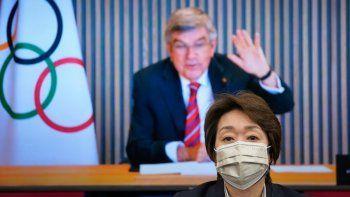 En esta foto del 28 de abril de 2021, el presidente del COI Thomas Bach en un pantalla saluda a la presidenta del comité organizadora de los Juegos de Tokio Seiko Hashimoto al comienzo de una reunión.