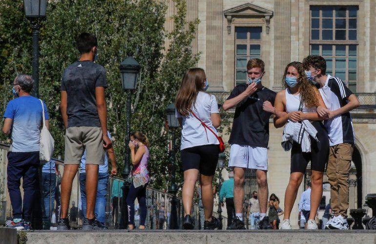 Personas con mascarillas protectoras caminan junto al Museo del Louvre en París el viernes