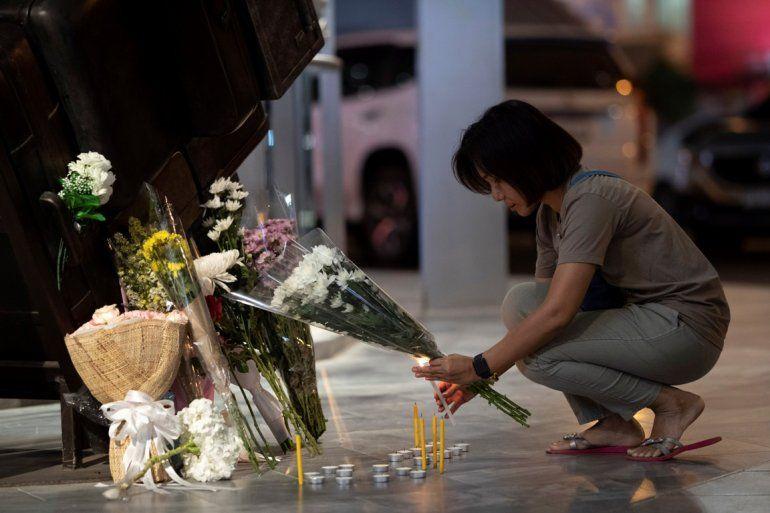 Una mujer enciende una vela en el centro comercial Terminal 21 Korat