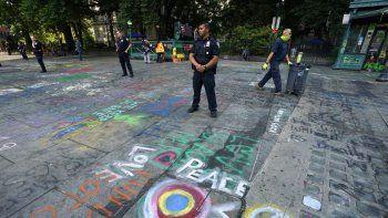 Los trabajadores de saneamiento limpian la basura y usan una lavadora a presión para eliminar graffiti que dejaron manifestantes que permanecieron durante un mes frente al Ayuntamiento, el 22 de julio de 2020, en Nueva York.