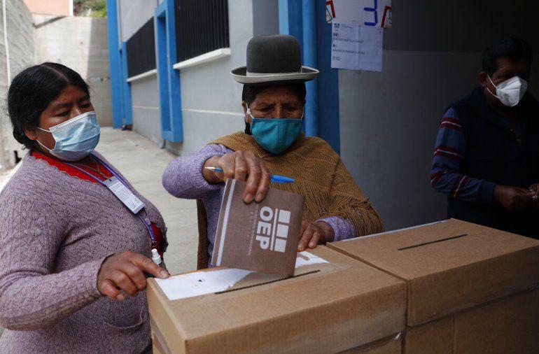Una mujer aymara con una máscara en medio de la pandemia de coronavirus espera para emitir su voto en un colegio electoral durante las elecciones regionales en El Palomar