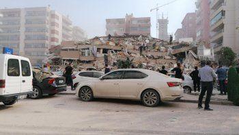 La gente trabaja en una casa derrumbada en un área afectada por el terremoto de Izmir, el 30 de octubre de 2020, luego de que un gran terremoto de magnitud 7.0 sacudiera la costa occidental de Turquía.