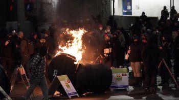 Un contenedor de basura arde en una protesta contra la violencia policial, la noche del domingo 24 de enero de 2021 en el centro de Tacoma, Washington, al sur de Seattle. La protesta se celebró al día siguiente de que un auto patrulla arremetiera contra una multitud, hiriendo a dos personas.