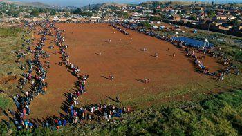 Centenares de personas hacen fila para recolectar alimentos en un centro de distribución en el asentamiento informal de Itereleng en Pretoria, Sudáfrica, el miércoles 20 de mayo de 2020, cuando el país cumplía 55 días de confinamiento soocial ordenado por el gobierno para evitar la propagación del coronavirus.